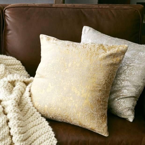 Блестящие подушки и вязанный плед для дивана