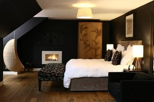 Красивая спальня с черными обоями и подвесным креслом