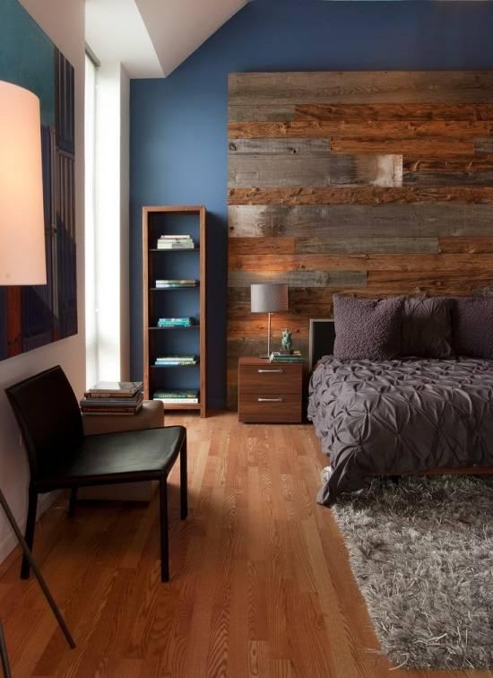 Большое деревянное изголовье и стильная мебель в  спальне