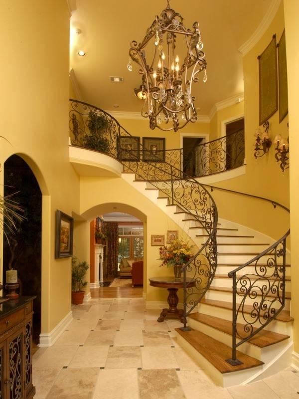 Большая кованая люстра перед лестницей в холле