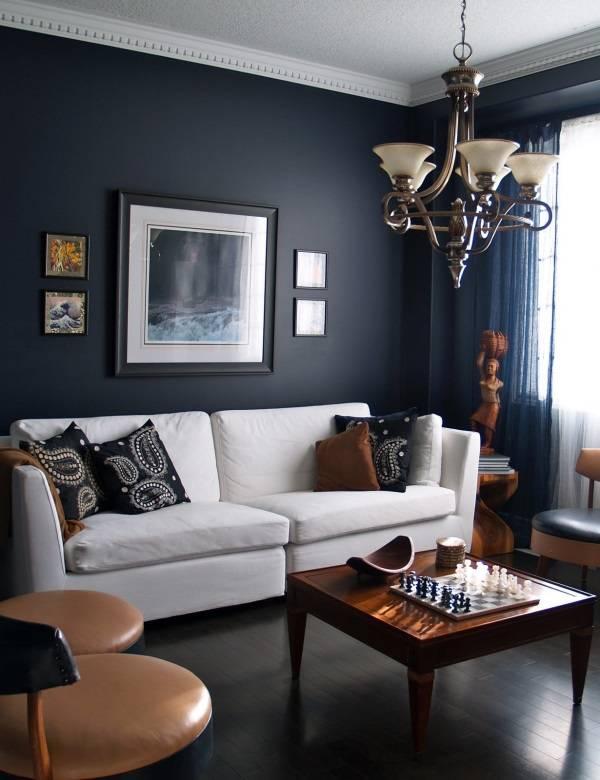 Oturma odasında karanlık duvarlar ve beyaz bir kanepe