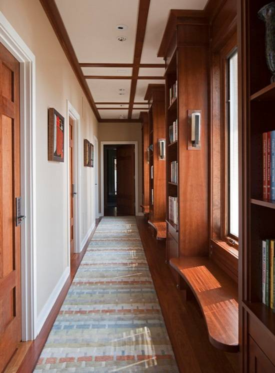 Домашняя библиотека в коридоре с окнами