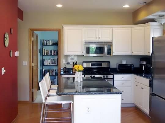Белая кухня с красной стеной и барной стойкой