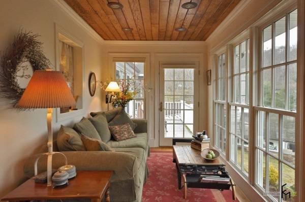 Застекленная веранда с большим диваном и светильниками
