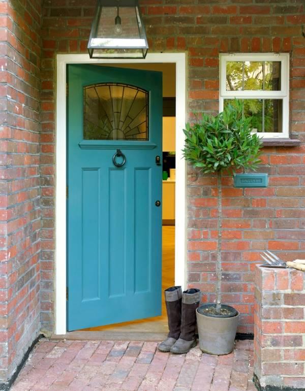 Синие входные двери в красный кирпичный дом