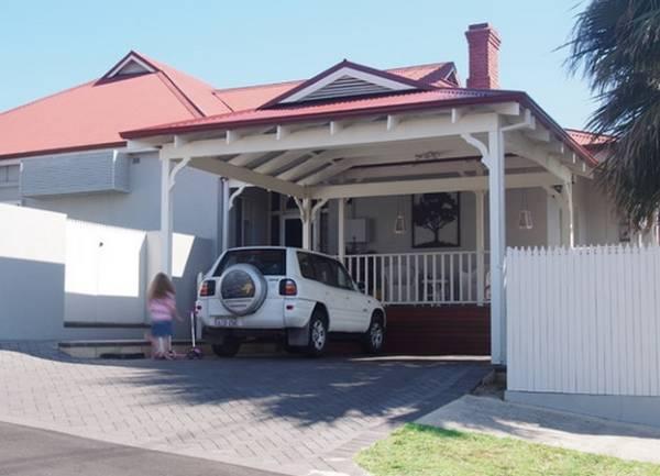 Дизайн дома с навесом над верандой и машиной