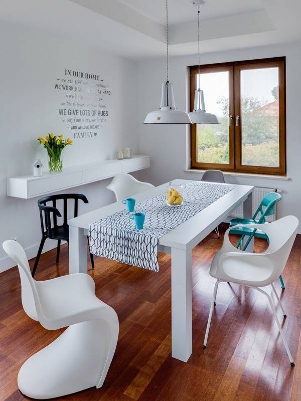 Белый обеденный стол и разноцветные стулья