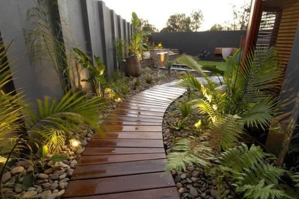 Деревянные дорожки с галькой и подсветкой возле дома