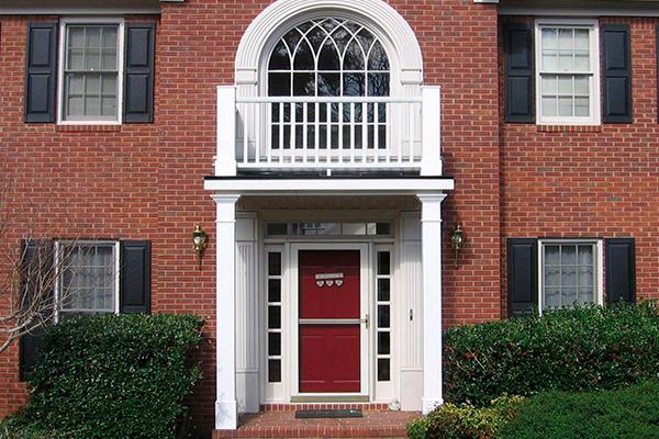 Белая лепнина на фоне фасада из красного кирпича