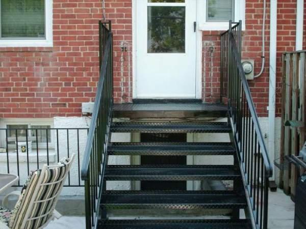 Маленькое металлическое крыльцо с лестницей к кирпичному дому