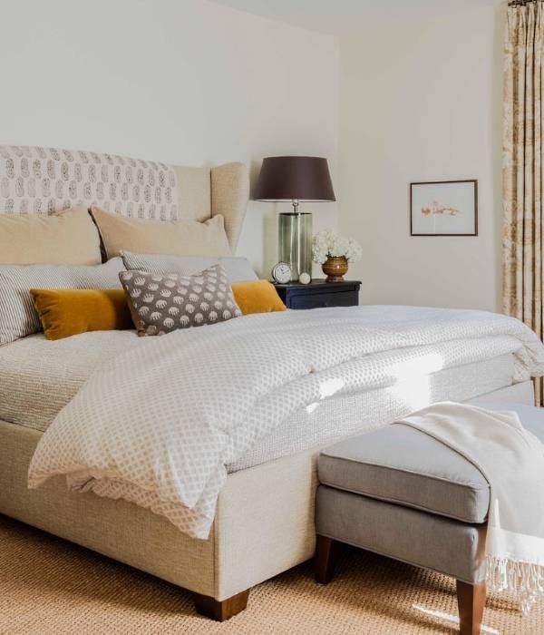 Интерьер спальни в бежевых тонах с добавлением серого и оранжевого