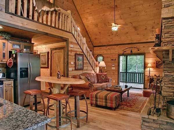 Интерьер гостиной в деревянном доме с лестницей на второй этаж