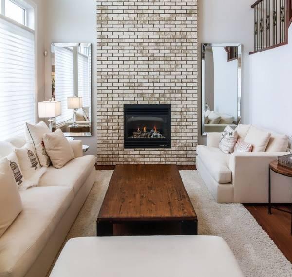 Стильный интерьер гостиной с белой мебелью и деревом
