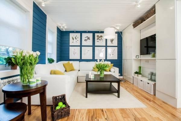 Белый диван в интерьере с синими обоями и деревянным полом