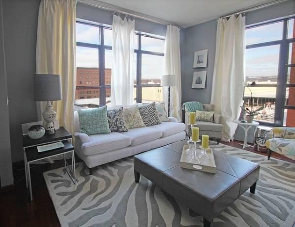 Белый диван в гостиной с серыми стенами