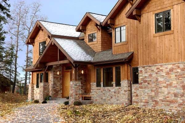 Отделка фасада частного дома панелями под камень и дерево