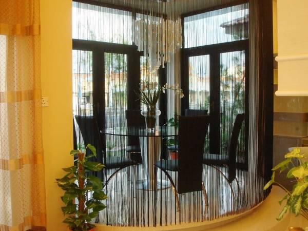 Черные нитяные шторы в интерьере кухни с эркером