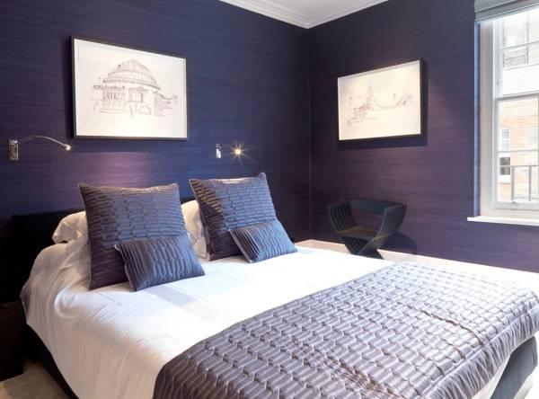 Интерьер маленькой спальни с темными фиолетовыми стенами