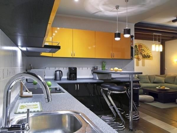 Угловой кухонный гарнитур с барной стойкой в квартире студии