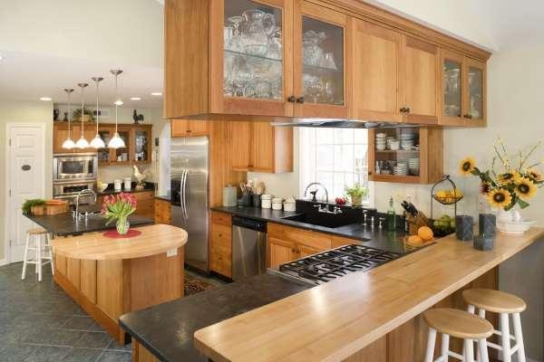 Современный дизайн угловой кухни с остром и барной стойкой из дерева - фото в частном доме