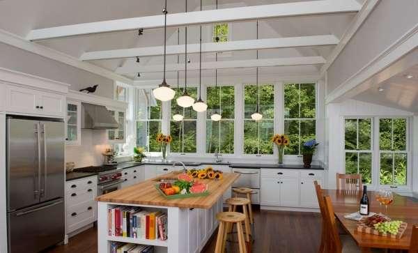 Интерьер большой кухни с окном в частном доме загородом