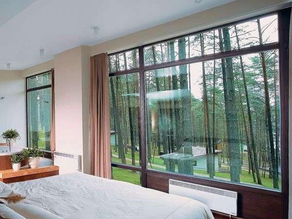 Спальня с большими окнами внутри частного дома