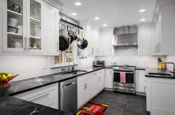 Черно белая кухня с белыми шкафами и темной столешницей