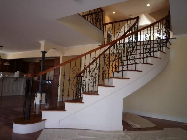 Красивая лестница из бетона с коваными перилами в интерьере частного дома