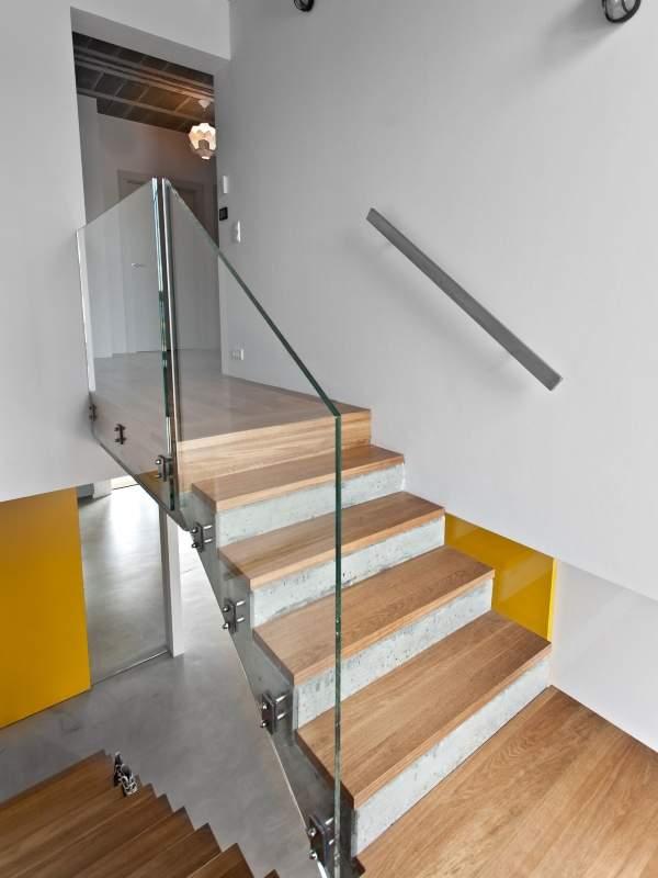 Бетонная лестница с деревянными ступенями и стеклянными перилами в частном доме