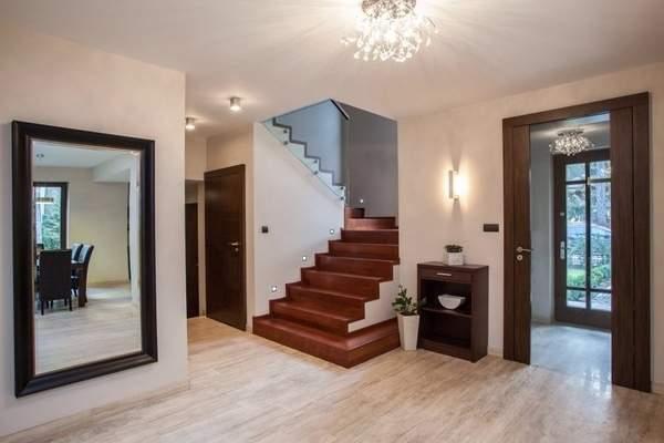Дизайн прихожей в частном доме с большими зеркалами и лестницей