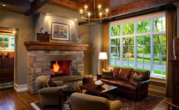 Интерьер деревянной гостиной с камином в частном доме из камня