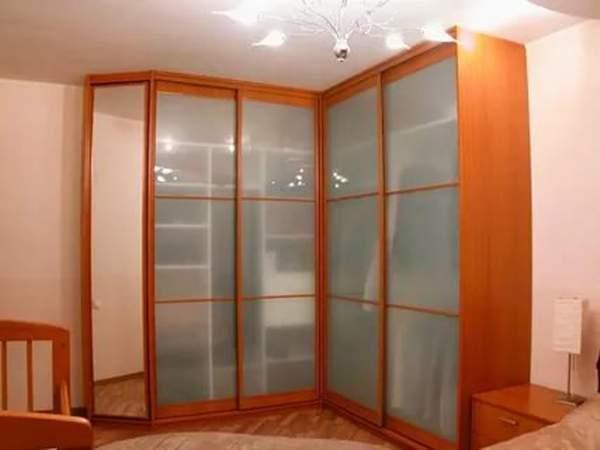 Г-образный угловой шкаф купе из ДСП со стеклянными дверями в спальне