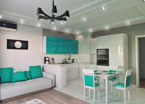 бело-бирюзовый интерьере гостиной объединённой с кухней с островом