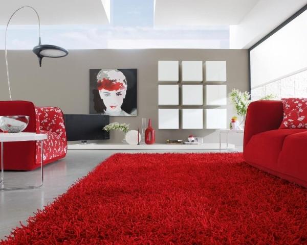 эффектная гостиная с ярко красным ковром на полу и красными диванами