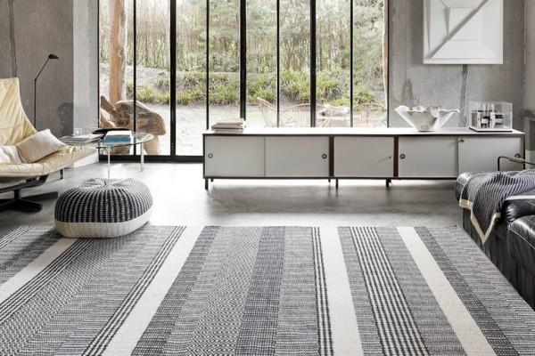 эффектное дополнение интерьера гостиной в серых тонах ковром на полу