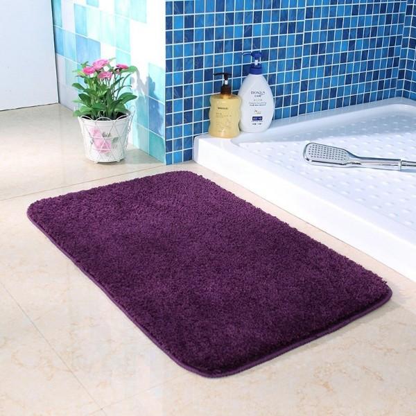 коврик фиолетового цвета на полу в ванной комнате
