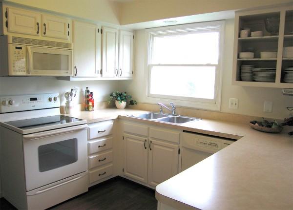 светлый дизайн маленькой угловой кухни с мойкой у окна