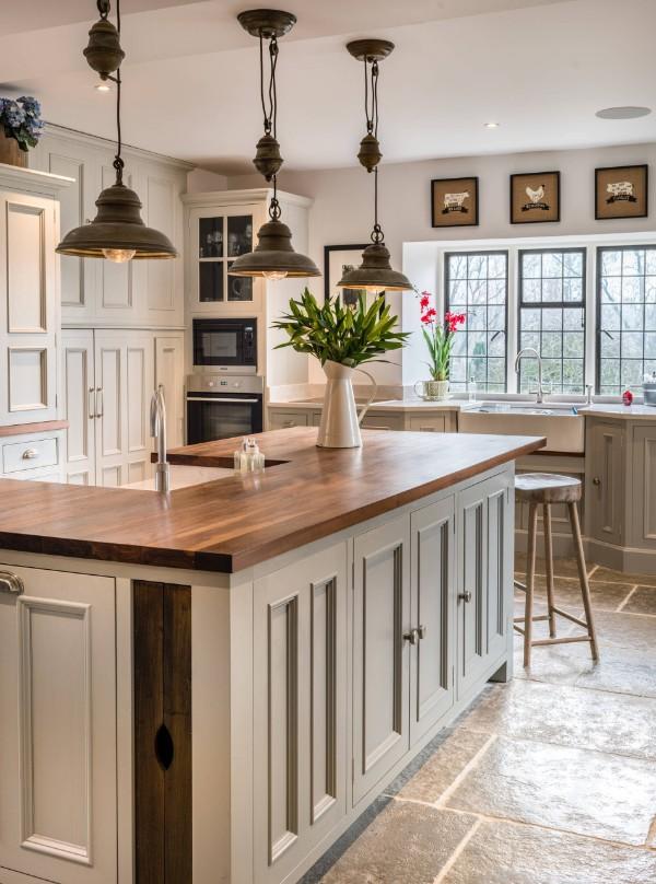 шикарная белая кухня во французском стиле с металическими светильниками