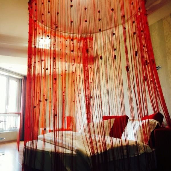 шторы нити красного цвета с узелками в интерьере спальни