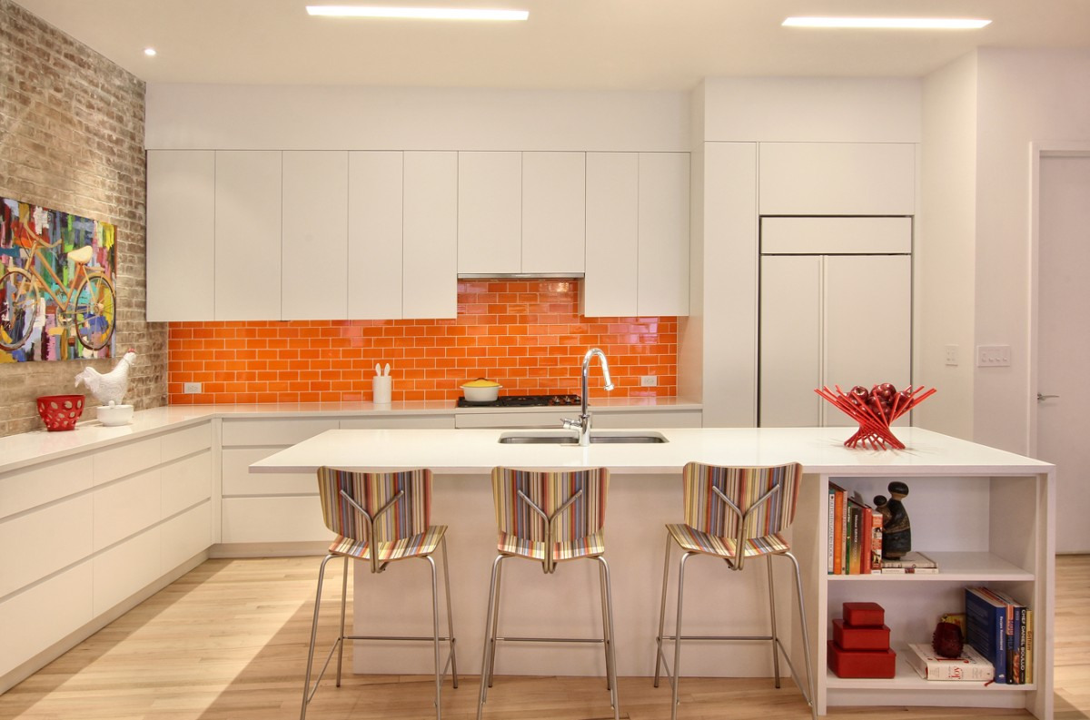 белая кухня с яркими акцентами в виде оранжевого фартука и спинок стульев