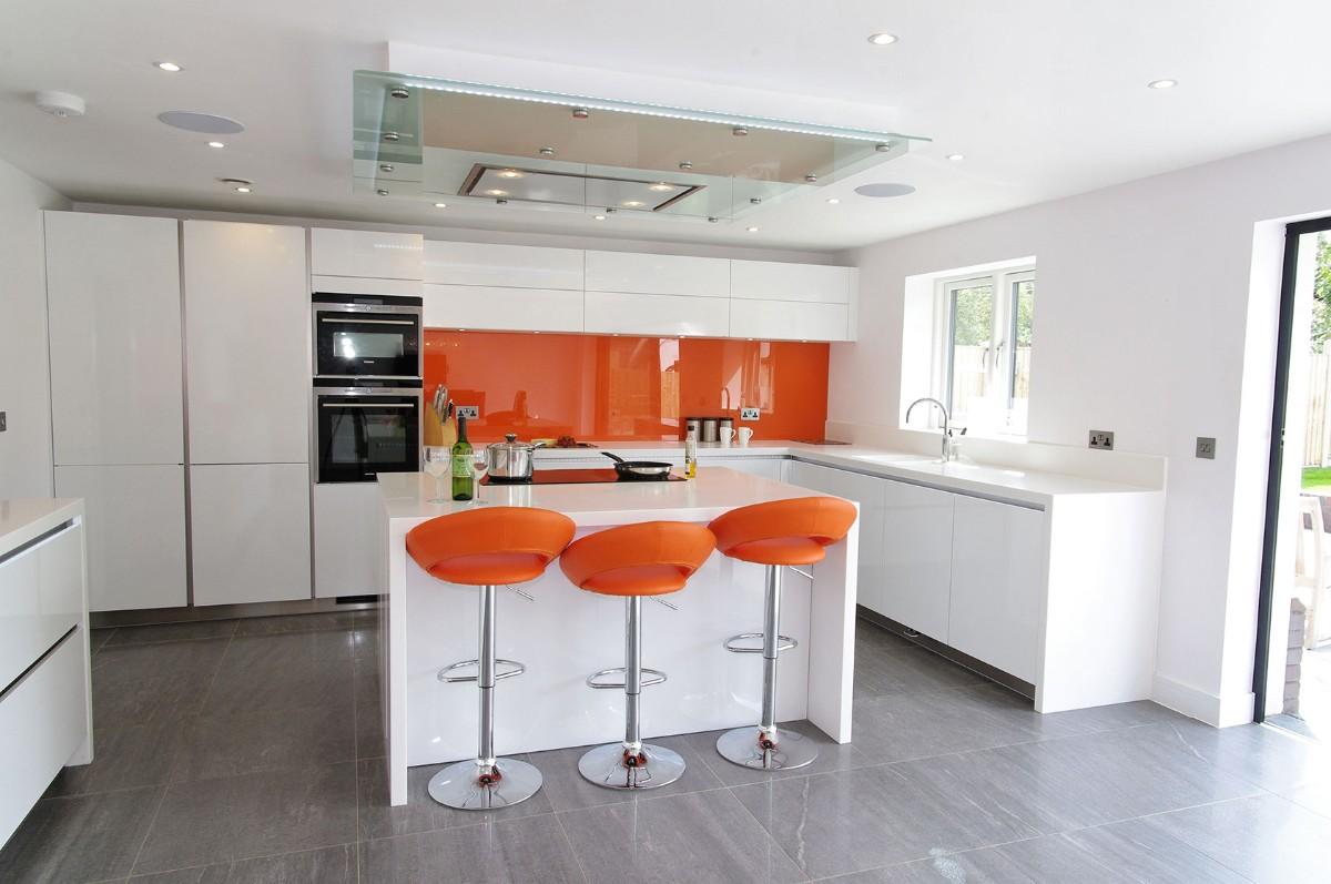 современная белая кухня с ярким акцентом оранжевые барные стулья