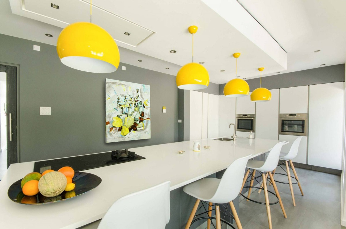 светло-серая кухня с яркими акцентами в виде жёлтых плафонов