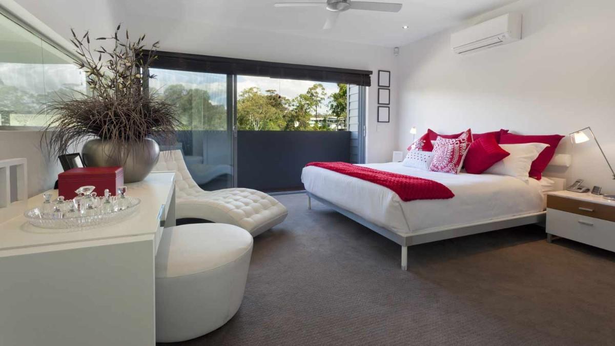 просторная спальня в белом цвете с красными акцентами