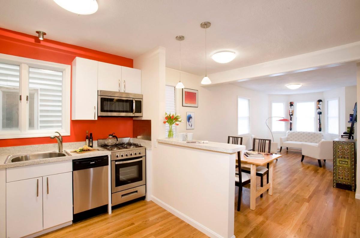 светлый дизайн кухни гостиной с яркой акцентной стеной в частном доме