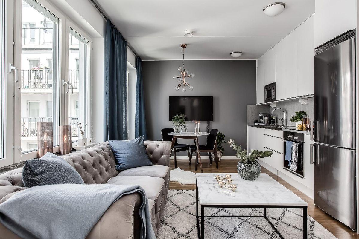 интерьер маленькой квартиры студии серо-белый дизайн с синими портьерами