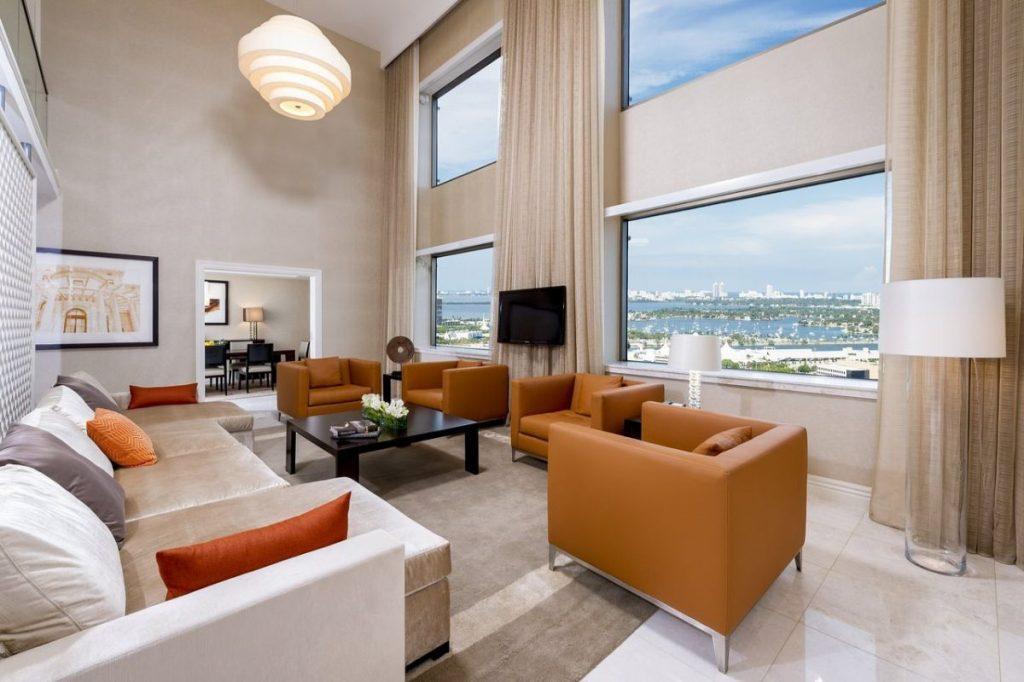 нюдовый интерьер в гостиной с высоким потолком